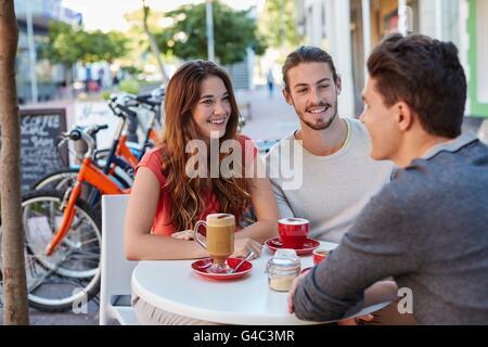 -MODELL VERÖFFENTLICHT. Drei jungen Freunden im Café mit heißen Getränken, lächelnd. - Stockfoto