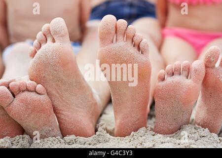 -MODELL VERÖFFENTLICHT. Familie am Strand, Fokus auf nackten Füßen sitzen. - Stockfoto