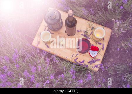 Kleiner Tisch mit Flasche Wein für Engagement im Lavendelfeld dekoriert. - Stockfoto