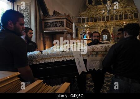 Männer tragen einen Sarg in die Kirche von Agios Ioannis für eine Trauerfeier in Anogia auf Kreta in Griechenland - Stockfoto