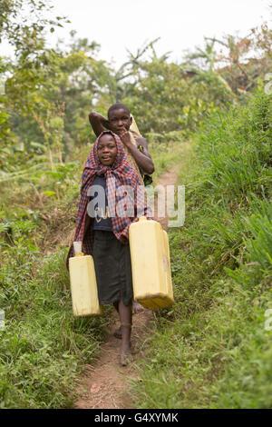 Kinder tragen Gießkannen ein Dorf Weg in Kasese District, Uganda, Ostafrika. - Stockfoto
