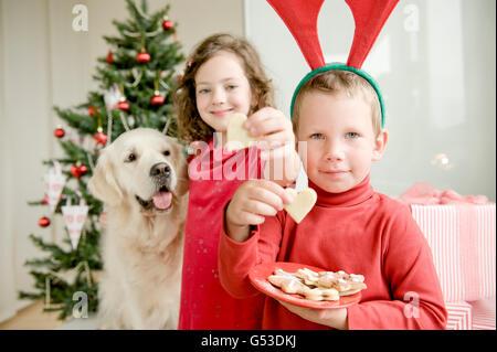 Ein Mädchen und einen jungen Elch Geweih Essen Weihnachtsplätzchen vor einem Weihnachtsbaum, ein Golden Retriever - Stockfoto