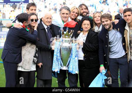 Manchester City Manager Roberto Mancini (Mitte), mit einer italienischen Flagge gehüllt, feiert mit seinem Vater Aldo (4. Links), seiner Frau Federica (6. Rechts) und seiner Mutter Marianna (4. Rechts) die Barclays Premier League Trophy