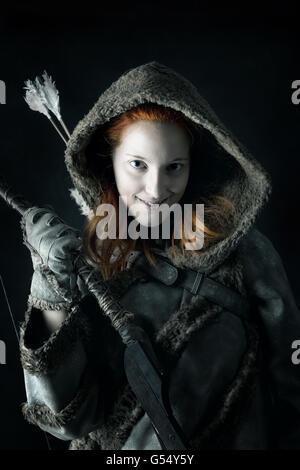 Mädchen Bogenschütze in einem Kostüm mit Bogen in einem dunklen Hintergrund isoliert - Stockfoto