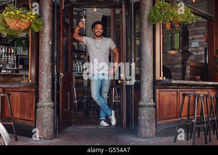 In voller Länge Portrait von lächelnden jungen Mann stand an der Tür eines Cafés. Entspannte moderne Jüngling in - Stockfoto