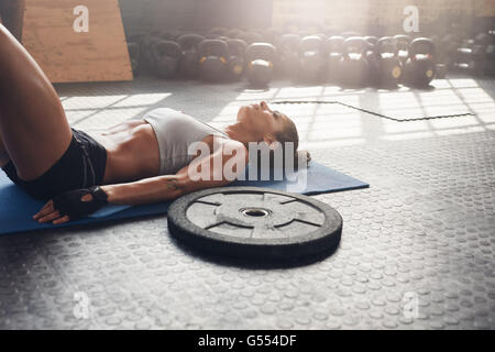 Fitness-Frau nach ihrem Training im Fitnessraum entspannen. Schwere Platte Stock mit muskulöse Frau liegend auf - Stockfoto