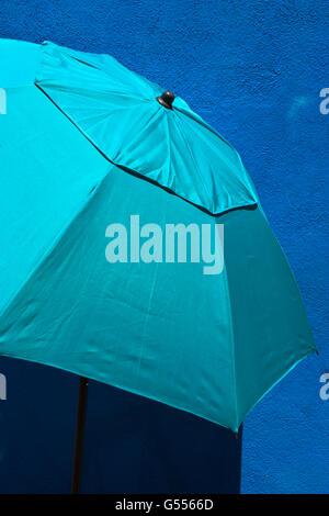 Türkis Sonnenschirm vor einer blauen Wand, Mandracchio, Burano, Lagune, Veneto, Italien - Stockfoto