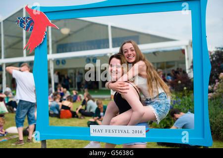 Zwei Mädchen im Teenageralter posiert für ein Foto in einem Frame bei der jährlichen The Hay Festival of Literature - Stockfoto
