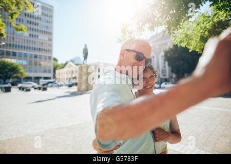 Glückliche und liebevolle älteres paar umarmt und unter einem Selfie im Freien. Touristen, die Einnahme von Selbstporträts - Stockfoto