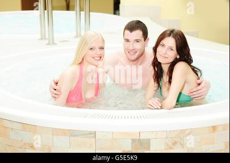 Junger Mann und zwei junge Frauen sitzen im whirlpool - Stockfoto