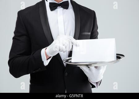 Nahaufnahme von Butler in Smoking und Handschuhe halten leere Karte auf Tablett - Stockfoto