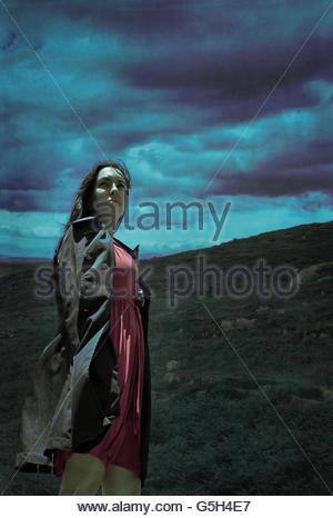 Windige Frau im schwarzen Mantel - Stockfoto