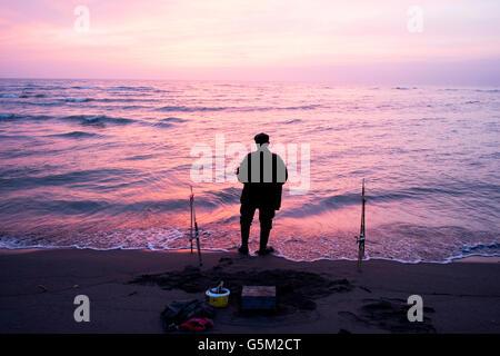 Ein Mann Angeln, während die Sonne untergeht. Schöner Sonnenuntergang an der Adria. - Stockfoto