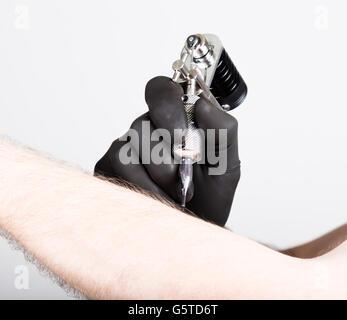 Nahaufnahme der Tätowierer Hände in schwarzen Handschuhen mit Tattoomaschine - Stockfoto
