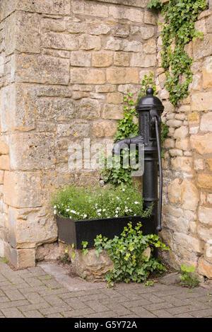 Alte gusseiserne Handpumpe Wasser und Trog mit Blumen auf der Straße in in Chipping Campden, Gloucestershire, England