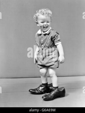 1930S 1940S UNTER DER LEITUNG LAUGHUNG LOCKIGEN BLONDEN JUNGEN ERWACHSENEN SCHUHE VATERS FUßSTAPFEN WANDERBARES - Stockfoto