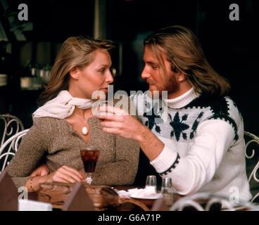 1970ER JAHREN ROMANTISCHES PAAR MANN FRAU MIT GETRÄNKE IM CAFÉ IM FREIEN SITZEN BEIDE TRAGEN PULLOVER MANN HAT LANGE - Stockfoto