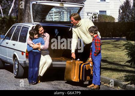 1980ER JAHRE VIERKÖPFIGE FAMILIE IMMER BEREIT FÜR DIE REISE-MUTTER UND TOCHTER SITZEN AUF AUTO HECKKLAPPE VATER - Stockfoto