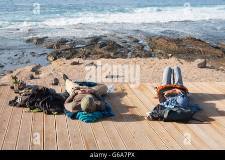 Männliche und weibliche Rucksacktouristen entspannen Sie sich auf Holzsteg mit Blick auf Surf-Strand in Las Palmas, - Stockfoto