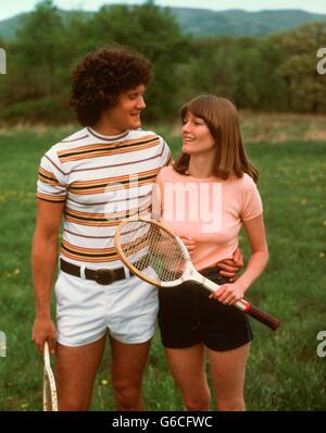 1970S 1980S PAAR TRAGEN TENNIS SHORTS HOLDING SCHLÄGER - Stockfoto