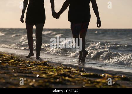 Ein paar hand in hand gehen entlang an einem tropischen Strand - Stockfoto