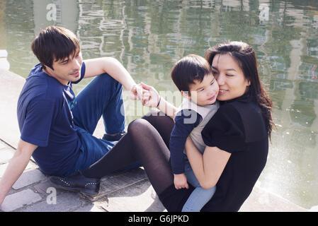 Eltern und Kind hängen am Ufer - Stockfoto