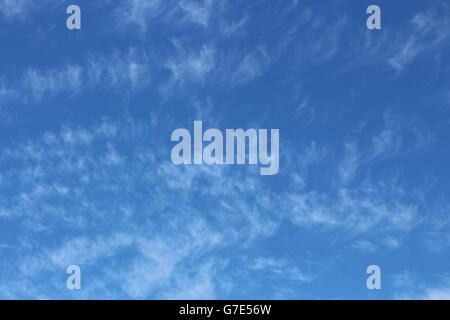 Whispy Cirrus Wolkenbildung vor einem blauen Himmelshintergrund - Stockfoto