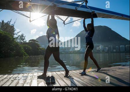 RIO DE JANEIRO - 22. März 2016: Nach der Ausbildung tragen zwei weibliche brasilianische Ruderer ihr Boot zurück - Stockfoto