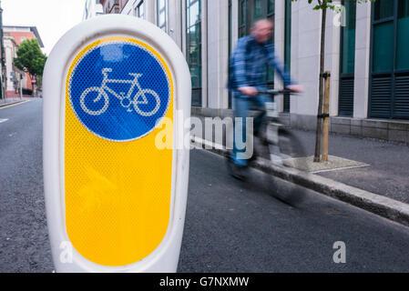 Ein Radfahrer Zyklen vorbei an einem Poller, teilt ein Radweg von der Hauptstraße entfernt. - Stockfoto