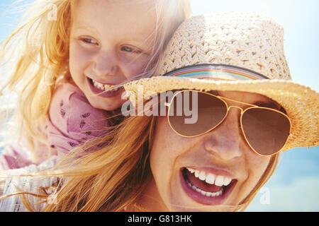 Junge Mutter in einer trendigen Hut und eine Sonnenbrille geben ihrer kleinen Tochter ein Huckepack im Freien in - Stockfoto