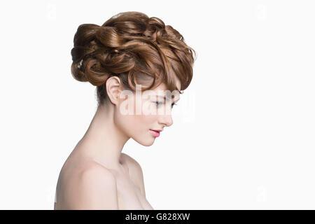 Seitenansicht der schönen Frau blickte auf weißen Hintergrund - Stockfoto