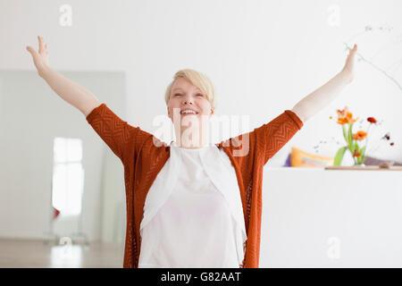 Lächelnd Mitte Erwachsene Frau mit ausgestreckten zu Hause - Stockfoto