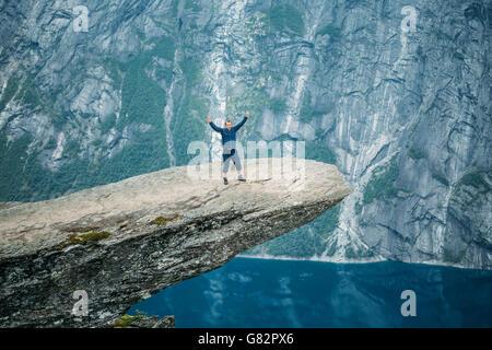 Junger Mann auf Felsen In den Bergen von Norwegen. Natürliche Sehenswürdigkeiten der Trolltunga - Troll Zunge. - Stockfoto