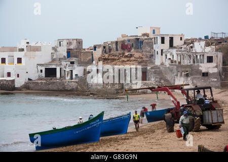 Ein Traktor hilft Fischerboote an Land in Tifnit Strand in der Nähe von Agadir, Marokko zu heben. - Stockfoto