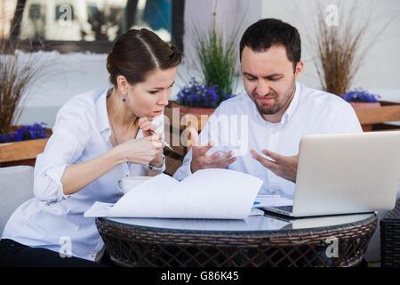Männlichen und weiblichen Kollegen gemeinsam an ein schwieriges Problem im Café im Freien. Sie sind Ausdruck auf - Stockfoto