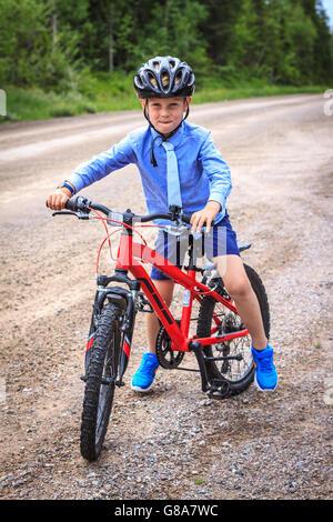 Formell gekleidet junge mit Krawatte, balancieren auf roten Mountainbike auf Schotterstraße. - Stockfoto