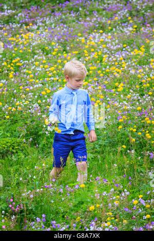 Junge Wandern in einer Wiese voller Blumen in verschiedenen Farben, ein Bündel in der Hand hält. Formelle Kleidung, - Stockfoto