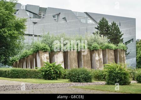 Berlin. Das jüdische Museum (Daniel Libeskind, 1999). Russische Olivenbäume wachsen in gekippter Betonpfeiler in - Stockfoto