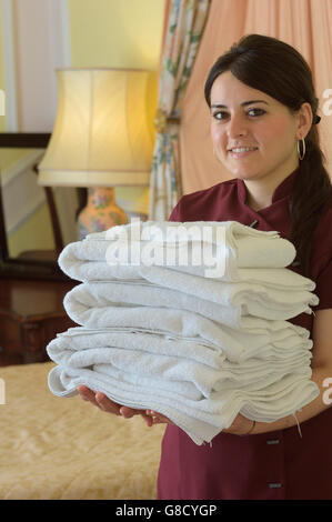 Zimmermädchen hält einen Stapel Handtücher - Stockfoto