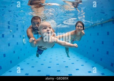 Glückliche vollständige Familie - Mutter, Vater, Sohn lernen, Schwimmen, Tauchen Sie unter Wasser mit Spaß im Pool, - Stockfoto