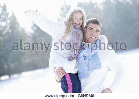 Vater und ein junges Mädchen spielen im Schnee, Porträt - Stockfoto