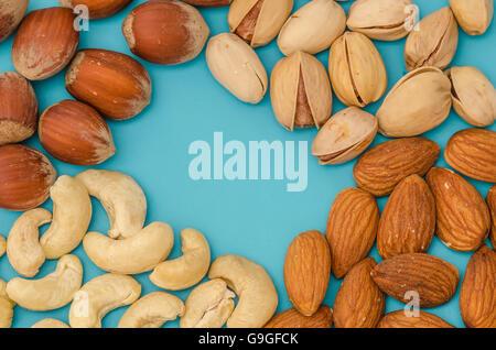 Gruppe von verschiedenen Nüssen isoliert auf blau - Stockfoto