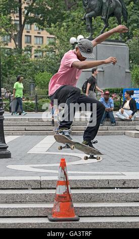 Skateboarder üben Sprünge über Leitkegel im Union Square Park in New York City - Stockfoto