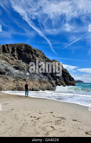 Ein Mann steht am Strand Kynance Cove Cornwall England UK - Stockfoto