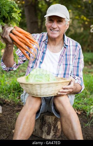 Porträt des Mannes mit Karotten und Kohl im Garten - Stockfoto