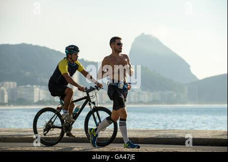 RIO DE JANEIRO - 3. April 2016: Jogger und Radfahrer Anteil der Radweg an der Strandpromenade Avenida Atlântica - Stockfoto