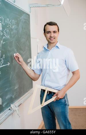 Junge Lehrer oder Schüler halten Dreieck auf Tafel mit Formel zeigen, auf die Kamera und lächelnd - Stockfoto