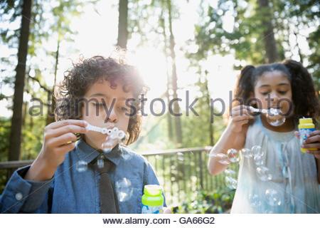 Jungen und Mädchen bläst Seifenblasen auf sonnigen Balkon in Wäldern - Stockfoto