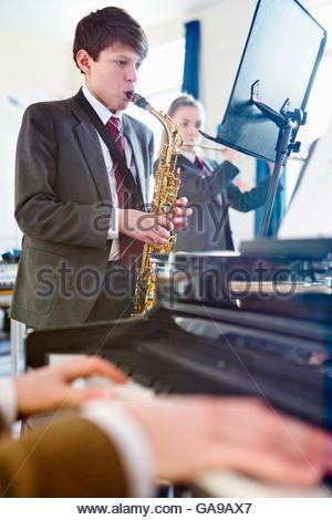 Schülerinnen und Schüler spielen Saxophon und Querflöte hinter Musiklehrer Klavier zu spielen - Stockfoto