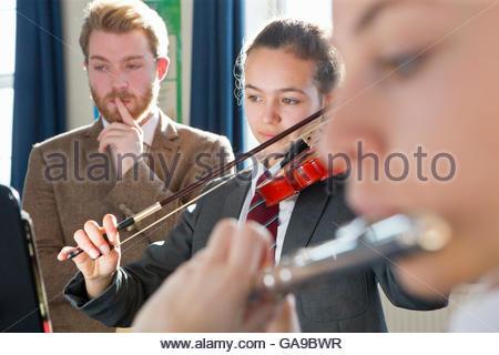 Lehrer unterrichten Schülerinnen und Schüler spielen Violine und Querflöte in Musik-Klasse - Stockfoto